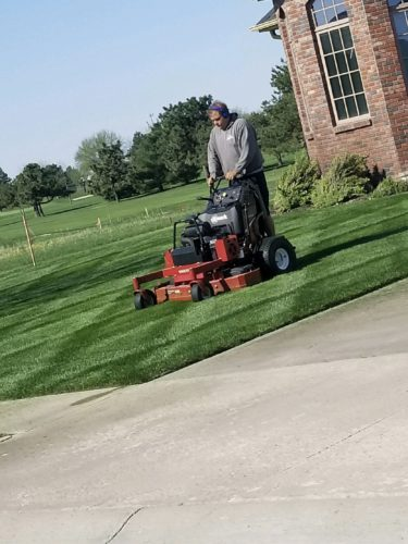 professional lawn care team mowing lawn